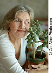 Senior woman with plant