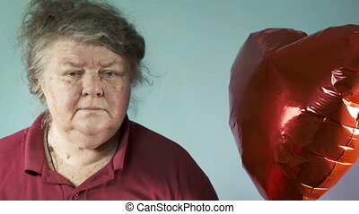 Senior woman with red heart balloon seventy year old woman looking at the camera