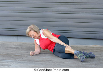Senior woman with severe muscle cramps in her calf clutching...
