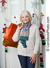 Senior Woman With Shopping Bags During Christmas