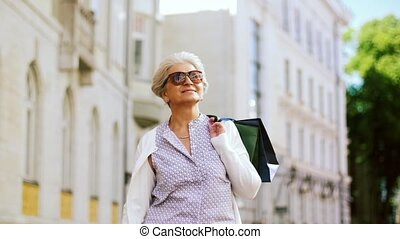 senior woman with shopping bags walking in city - sale,...