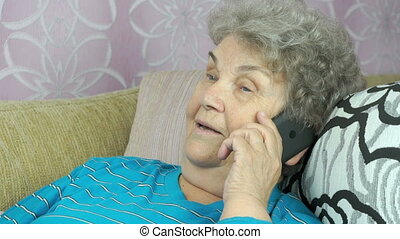Senior woman with smartphone calling at room