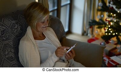 Senior woman with smartphone in front of Christmas tree.