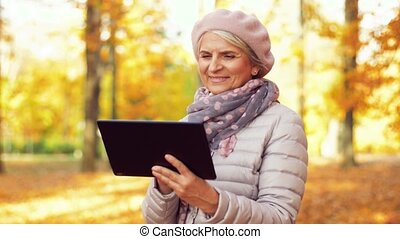 senior woman with tablet pc at summer park - technology, old...