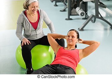 Senior woman with trainer exercising fitness ball
