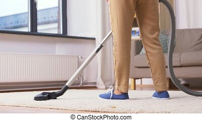 senior woman with vacuum cleaner cleaning at home