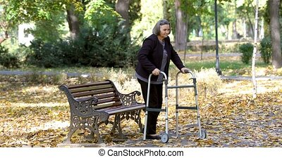 Senior woman with walker getting up and walking outdoors -...