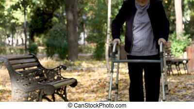 Senior woman with walker getting up from bench and walking outdoors