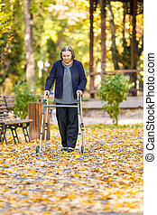 Senior woman with walker walking outdoors