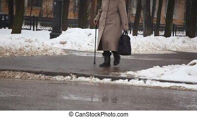 senior woman with walking-stick on winter street - Senior...