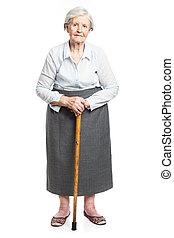 Senior woman with walking stick standing on white - Senior...