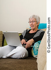 Senior woman working on a laptop, sitting relaxed on the couch.