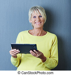 Senior woman working on a tablet and smiling