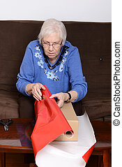 senior woman wrapping christmas gif