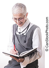 Senior woman writing in her notebook or diary