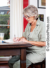 Senior woman writing notes at home