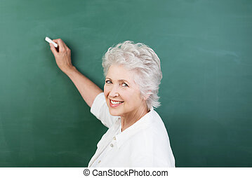 Senior woman writing on a chalkboard