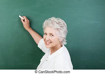 Senior woman writing on a chalkboard