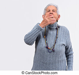 Senior woman yawning on white background