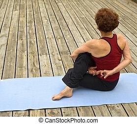 senior woman yoga - senior woman doing yoga on a deck floor