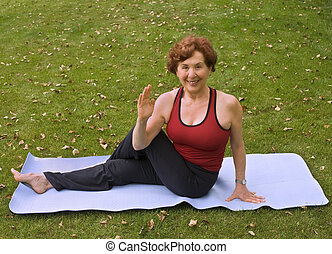 senior woman yoga - senior woman doing yoga on the grass