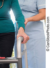 Senior Woman's Hands On Walking Frame With Care Worker In Background