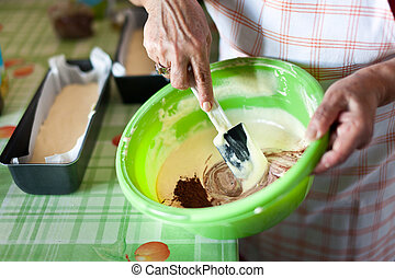 Senior woman's hands stirring cocoa cream with spatula -...