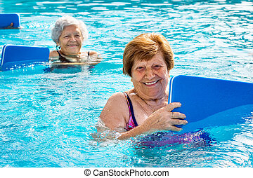 Senior women doing aqua exercise with kick boards. - Close...