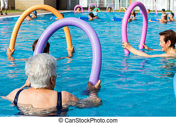 Senior women doing exercise with soft foam noodles in pool.