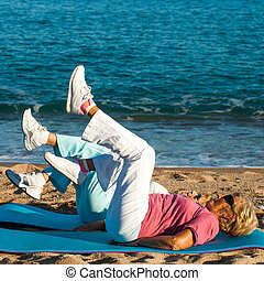 Senior women doing leg exercises on beach.
