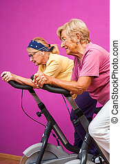 Senior women doing spinning in gym