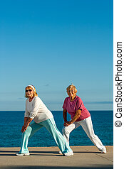 Senior women doing stretching exercise at seafront.