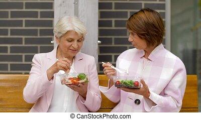 senior women eating takeaway food on city street - old age,...