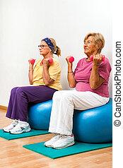 Senior women exercising in gym.