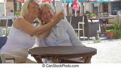 Senior women friends taking selfie in street cafe