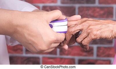 senior women hand using pulse oximeter,
