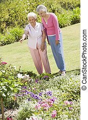 Senior women in garden admiring flowerbeds