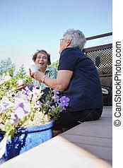 Senior Women Laughing Together - Two senior women in back...