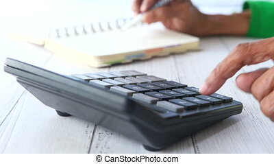 senior women omen hand using calculator and writing on notepad ,