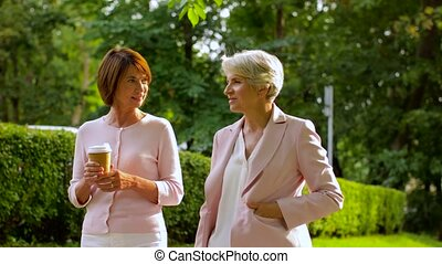 senior women or friends drinking coffee at park - old age,...
