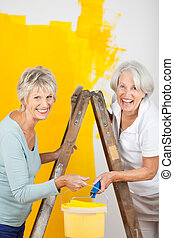 Senior Women Painting Wall Together - Portrait of happy...