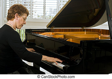 senior women pianist playing on a grand piano