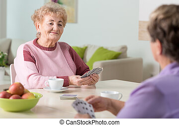 Smiling senior women playing cards at home