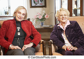 Senior women relaxing in armchairs