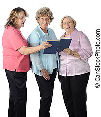 Senior Women Sing - Three senior women singing togethr from...