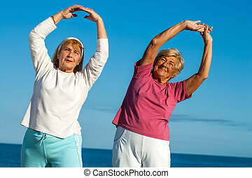 Senior women stretching arms outdoors.
