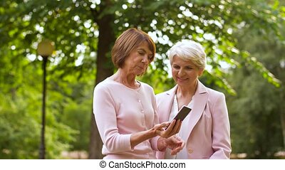 senior women taking selfie by smartphone at park -...