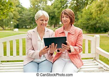 senior women with tablet pc at summer park