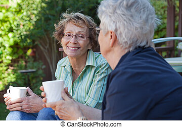 Senior Women with Warm Drinks - Two senior women enjoying a...