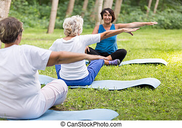 Senior women working out in a park with trainer